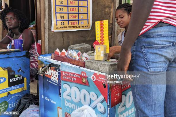 A street vendor sells prepaid mobile phone credit scratch cards in Accra Ghana on Thursday March 15 2018 Ghana wants to shake up the way it collects...