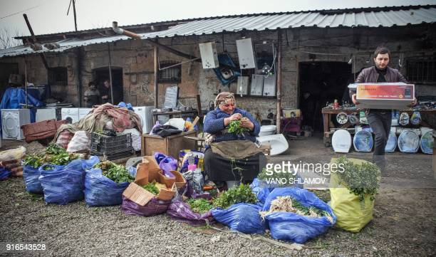 A street vendor sells salads and greenery at a small marketplace in central Tbilisi on February 10 2018 / AFP PHOTO / Vano Shlamov