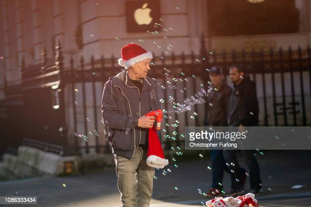 A street vendor sells Santa hats and a bubble machine as shoppers make their last minute purchases on Christmas Eve on December 24 2018 in Birmingham...