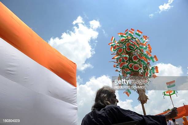 A street vendor sells trinkets adorned with the Indian Flag at the Indian Gate monument during Independence Day celebrations in New Delhi on August...