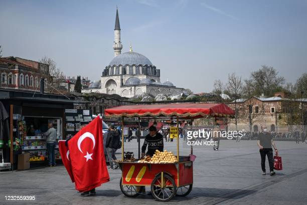 Street vendor sells Turkish national flags and corns in Istanbul's Eminonu district on April 27 two days ahead of a new full lockdown aiming at...