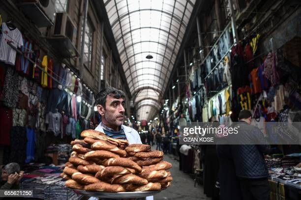 A street vendor sells Turkish traditional bakery 'Simit' on March 20 2017 at Mahmutpasa district in Istanbul On April 16 the Turkish public will vote...