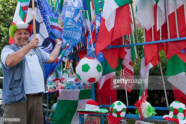 Street vendor sets up flags and gadgets at his stand ahead of the Euro 2012 final opposing Italy and Spain on July 1 2012 in the southern Italian...