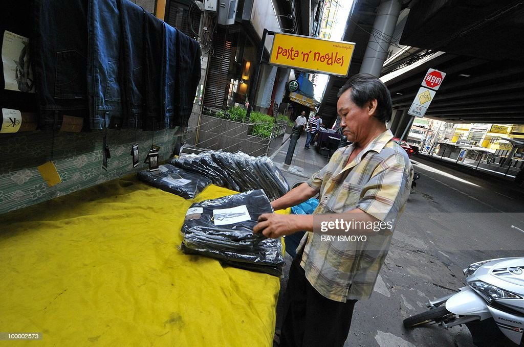 A street vendor sets up his products as life in the area gets back to normal after the recent violent confrontations between the 'Red Shirts' and the Thai army, in downtown Bangkok on May 20, 2010. Plumes of smoke hung overhead as Bangkok emerged from an curfew aimed at quelling mayhem unleashed by enraged anti-government protesters targeted in an army offensive on May 2010.