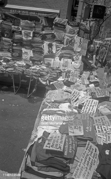 A street vendor sits with his stall of novelty tshirts in front of 637 9th Avenue in Hell's Kitchen New York New York May 14 1988