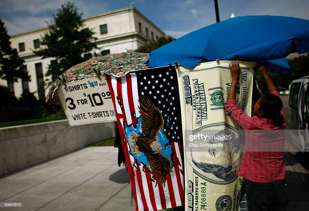 Street vendor Son Luom hangs a $100 bill beach towel from her stand just outside the Federal Reserve September 16, 2008 in Washington, DC. The Federal Open Market Committee (FOMC) met today and announced they will hold the federal funds rate at 2.0 percent, despite the recent turmoil among investment banks on Wall Street.