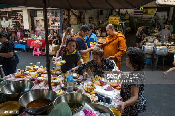 A street vendor tends to her cart of food offerings she has for sale at a local market in downtown Bangkok on February 22 2017 Buddhist followers buy...