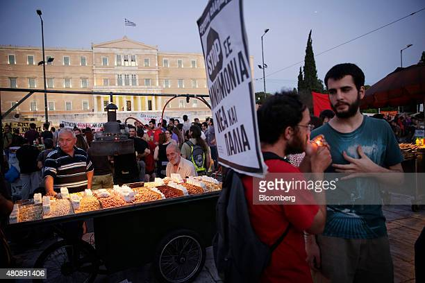 A street vendor waits for customers on Syntagma Square during a demonstration by antibailout protestors outside the Greek parliament in central...