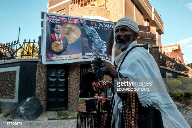 Street vendor walks in front of a billboard congratulating Ethiopia's Prime Minister Abiy Ahmed for his Peace Nobel Prize, in Addis Ababa on December...