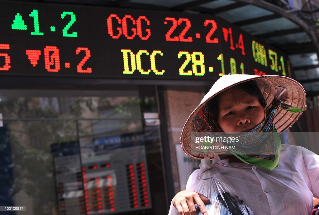 A street vendor walks past a local securities trading company in downtown Hanoi on May 21, 2010. The biggest drop in more than a year on Wall Street triggered fresh turmoil in Asian markets on May 21, amid heightened anxiety over the eurozone debt crisis and doubts over the strength of the US economy. Vietnam's stocks plunged 4.11 percent keeping its falling trend for weeks. AFP PHOTO/HOANG DINH Nam