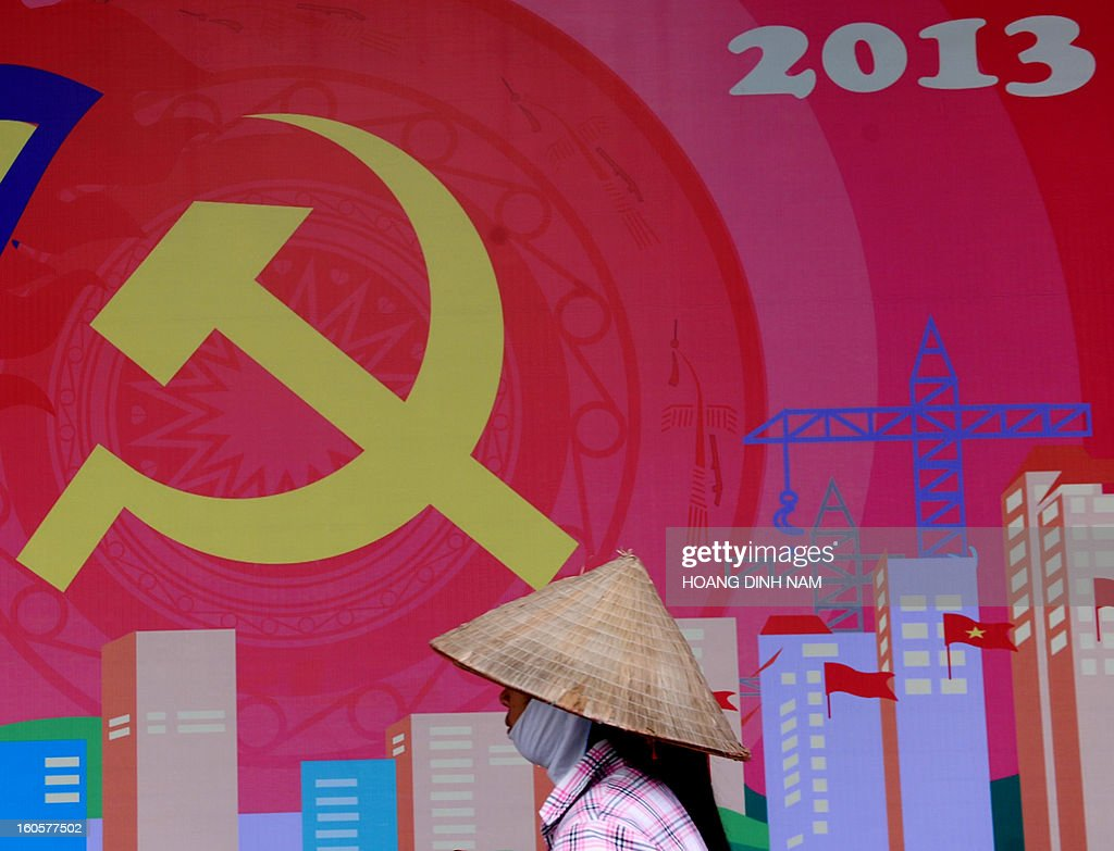 A street vendor walks past a poster marking the 83th anniversary of the foundation of Vietnamese Communist Party (VC) in downtown Hanoi on February 3, 2013. The rulling communist party celebrates its anniversary at a moment ou the Southeast Asian nation faces a serious financial and economic crisis with state-run companies are used to criticism and now accused of creating a systemic economic crisis which the communist regime connot fix. AFP PHOTO / HOANG DINH Nam