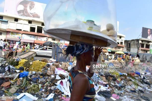 A street vendor walks past a trash heap at the market of Adjame a working class neighbourhood of Abidjan on August 10 2017 / AFP PHOTO / ISSOUF SANOGO