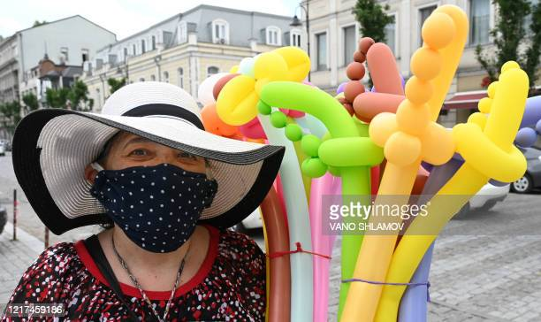 Street vendor wearing a face mask sells inflatable balloons in central Tbilisi on June 3 as Georgia lifted most of the restrictions on economic...