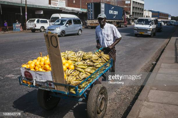 A street vendor wheels a cart containing fresh fruit produce for sale in Harare Zimbabwe on Tuesday July 31 2018 Zimbabwe's main opposition party...