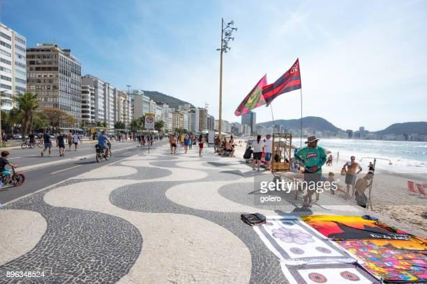 straßenhändler mit bunten kleidern am copacabana-strand - copacabana rio de janeiro stock-fotos und bilder