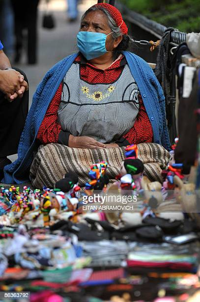 A street vendor woman wears a face mask trying to prevent contagion by the swine flu virus in Mexico City on April 30 2009 Officials tried to quell...
