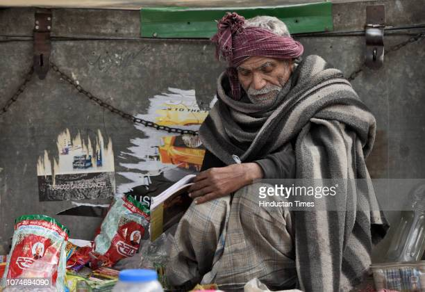 A street vendor wraps himself with a blanket to protect himself from cold on a winter morning near Baba Kharak Singh Marg on December 23 2018 in New...