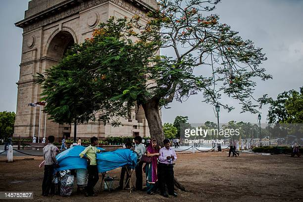 Street vendors and a couple seek refuge under a tree as they shelter from a rain shower at the India Gate monument on June 5 2012 in New Delhi India...