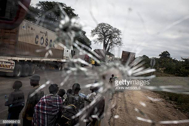 TOPSHOT Street vendors are seen through a bus windscren bullet hole alongside the Mozambican Main North South road on May 27 2016 at Nhamapaza in the...