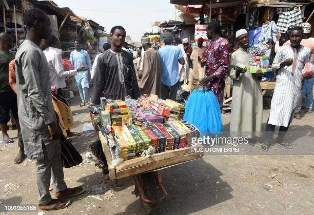 A street vendors carries goods at Sabon Gari Market in Kano on January 30 2019 Nigerian President Mohammadu Buhari has flag off campaign in Kano the...