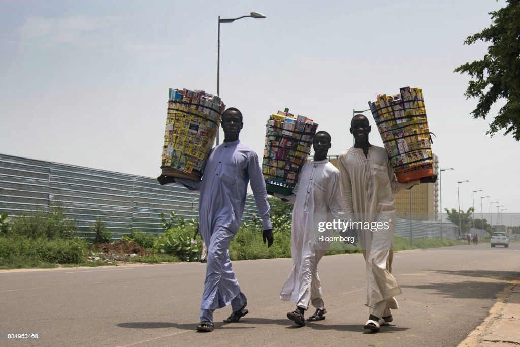 Street vendors carry baskets of medicines for sale in N'Djamena, Chad, on Wednesday, Aug. 16, 2017. African Development Bank and nations signed agreement to finance a project linking the town of Ngouandere in Cameroon and Chads capital, NDjamena, according to statement handed to reporters in Cameroonian capital, Yaounde in July. Photographer: Xaume Olleros/Bloomberg via Getty Images