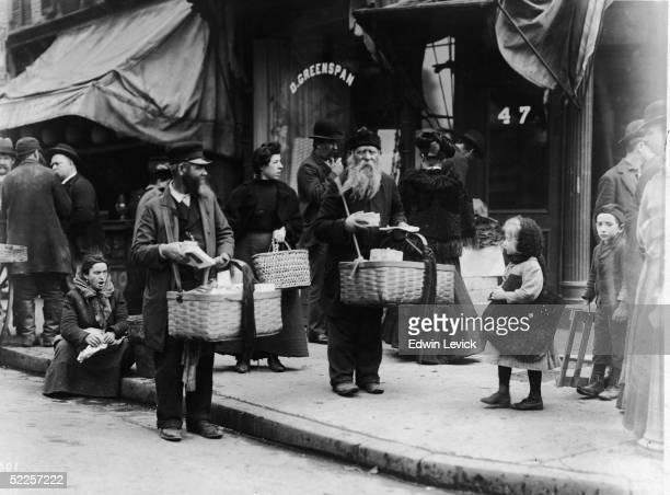 Street vendors carry their goods in baskets on a sidewalk on the Lower East Side New York 1900s