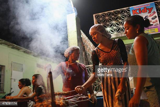Street vendors cook at the Parintins Folklore Festival in a town located along the Amazon River on June 27 2015 in Parintins Brazil The festival...