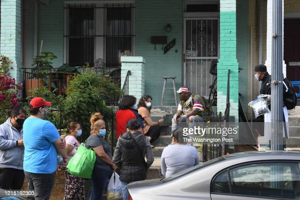 Street vendors join a line to get help with cash stipends, groceries and meals from Megan Macaraeg, with Many Languages One Voice , center, and other...