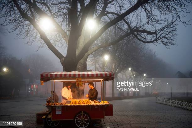 TOPSHOT Street vendors sell corn on Sultanahmet Square near the Blue mosque on a foggy day in Istanbul on February 20 2019