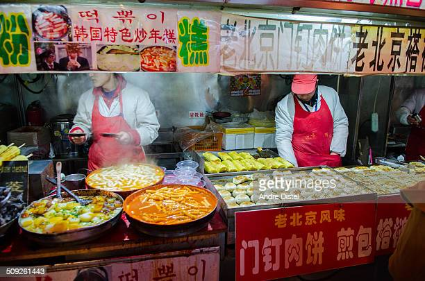 Street vendors selling exotic food to people passing by on Wangfujing Streets night market in Beijing China