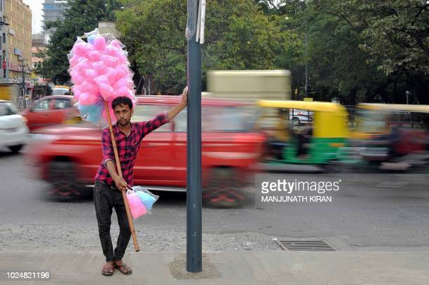 TOPSHOT A street vendors sells cotton candy at a busy traffic junction in Bangalore on August 28 2018