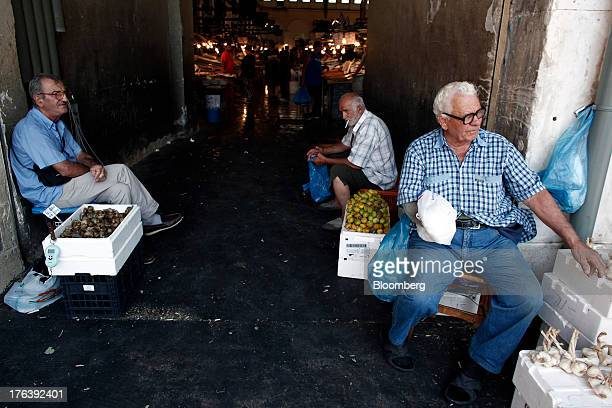 Street vendors sit beside their garlic right and shellfish products at the entrance to a fish market in Athens Greece on Friday Aug 9 2013 Greece's...
