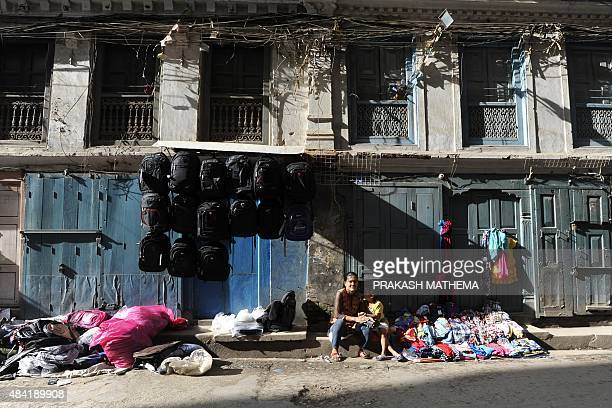 Street vendors sit on the sidewalk in front of closed shops during a general strike called by the 30party alliance led by a hardline faction of...