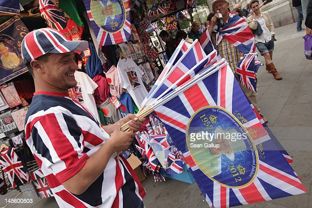 Street vendors tempt passersby with souvenir flags commemorating the Diamond Jubilee of Queen Elizabeth II at Trafalgar Square on June 2 2012 in...