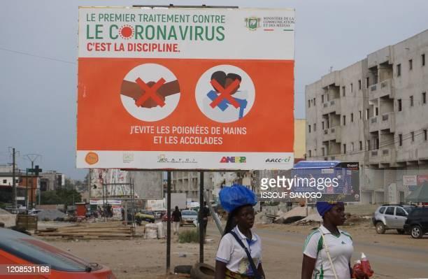 "Street vendors walk past a billboard reading ""The first treatment against coronavirus is discipline"" as part of a COVID-19 coronavirus awareness..."