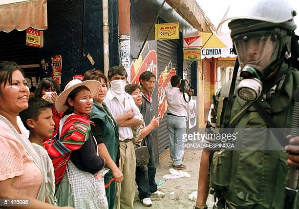 Street vendors yell at riot police 05 February in the center of Cochabamba, Bolivia, as riot police guard the main plaza from demonstrators...