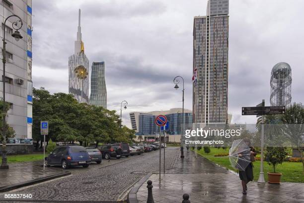a street view from batumi seaside with a woman walking with an umbrella . - emreturanphoto stock pictures, royalty-free photos & images