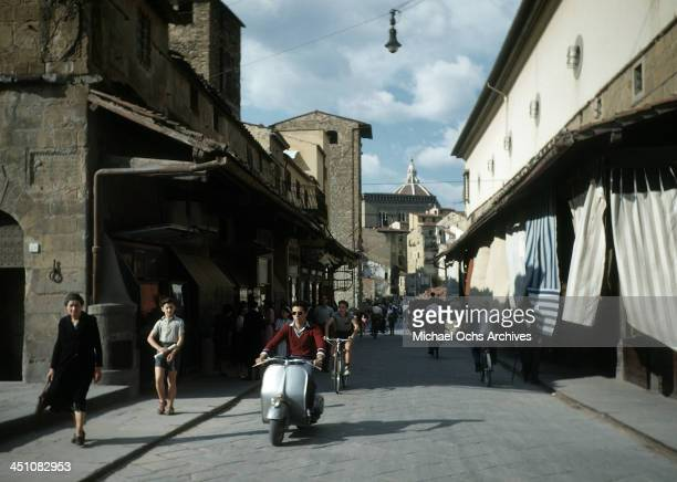 A street view of a man riding a Vespa in Florence Italy