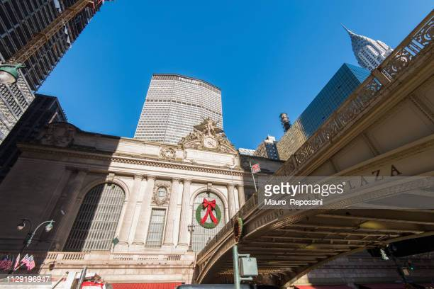 street view of grand central station, pershing square bridge, chrysler and metlife building during christmas season at manhattan, new york city, usa. - metlife building stock pictures, royalty-free photos & images
