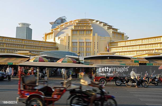 Street view of Phnom Penh's Central Market with tuk-tuks and other traffic.