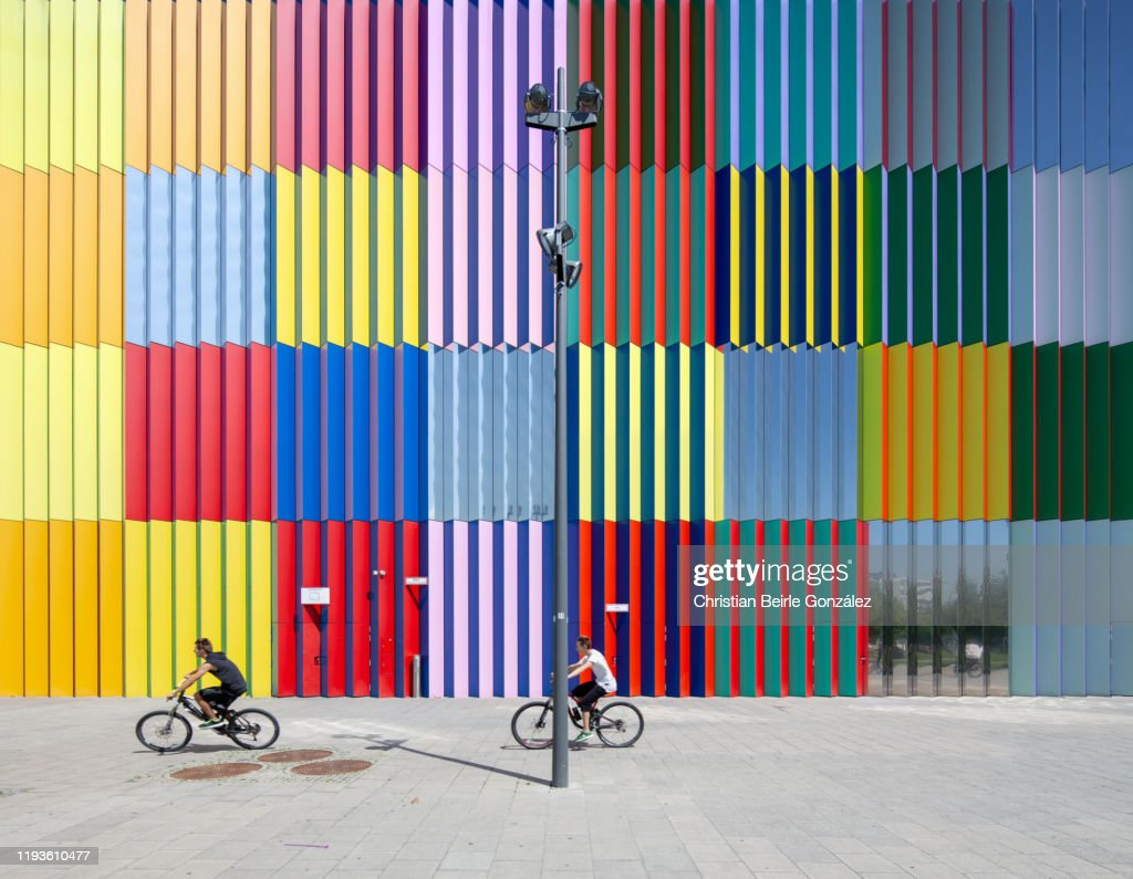 Street view of two teenagers riding bicycles in front of the MIRA shopping mall facade, Munich, Germany. : Stock-Foto