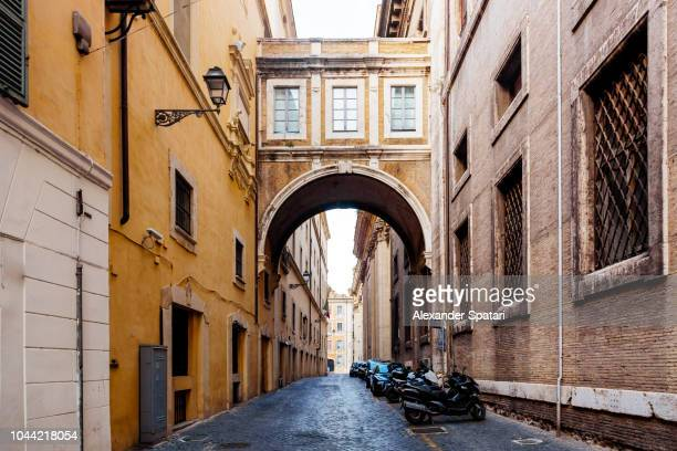 Street with arch in old town of Rome, Italy