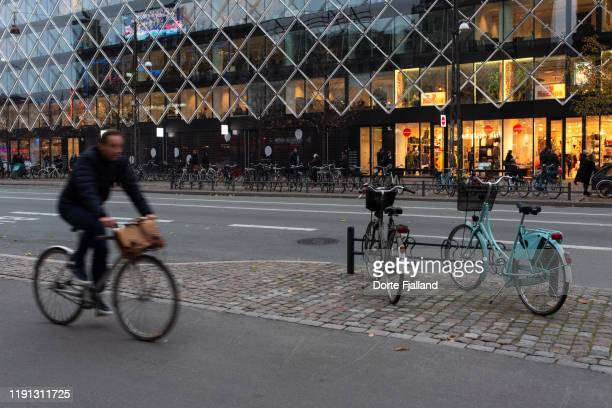 street with building with shops in the background and a man on a bike in the foreground - dorte fjalland stock pictures, royalty-free photos & images