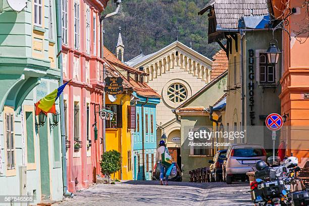 street with colorful houses and church, sighisoara - transylvania stock pictures, royalty-free photos & images