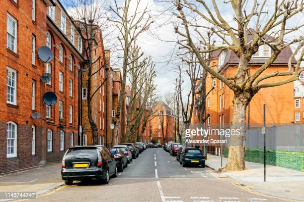 street with historical buildings and parked cars in shoreditch, london - shoreditch stock photos and pictures
