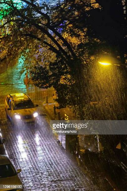 street with lamp and taxi under rain at night. - emreturanphoto stock pictures, royalty-free photos & images