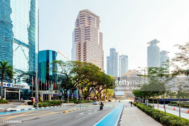 street with modern skyscrapers in kuala lumpur downtown on a sunny day with clear sky, malaysia - クアラルンプール ストックフォトと画像