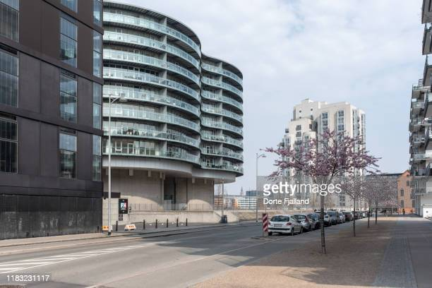 street with no traffic, some parked cars and new buildings on both sides - dorte fjalland stock pictures, royalty-free photos & images