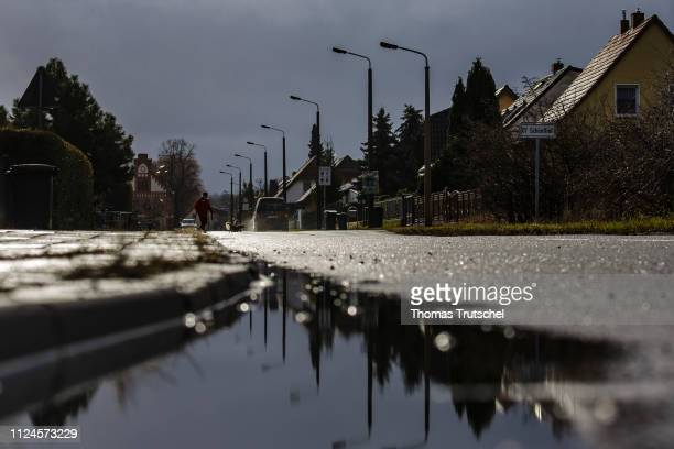 Street with one-family houses in the district Schoenfliess is reflected in a puddle on February 11, 2019 in Eisenhuettenstadt, Germany.