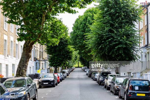 street with residential building and parked cars in primrose hill district, london, england, uk - parking stock pictures, royalty-free photos & images